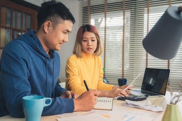 Un jeune couple asiatique gère les finances et examine ses comptes bancaires à l'aide d'un ordinateur portable