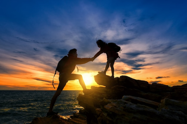 Jeune couple asiatique grimper sur la montagne au coucher du soleil.