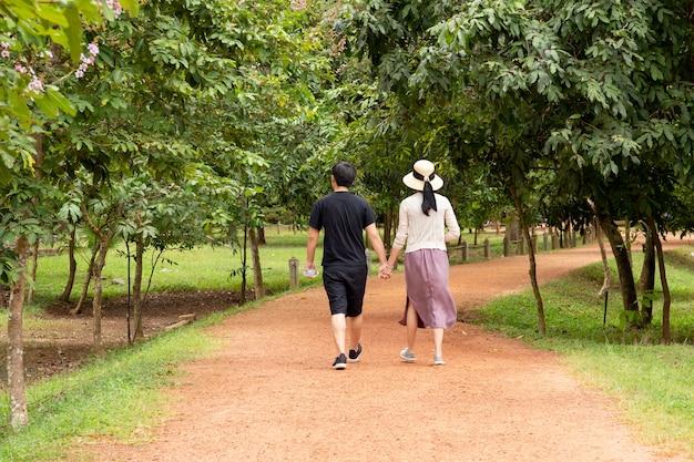 Jeune couple asiatique main tenant la main en marchant dans les bois en été.