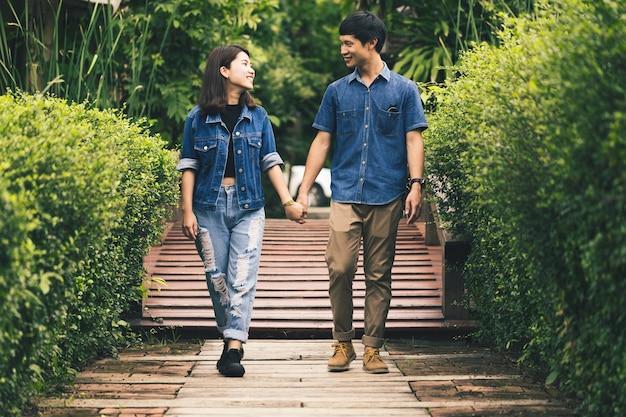 Jeune couple asiatique marchant dans l'amour dans la partk
