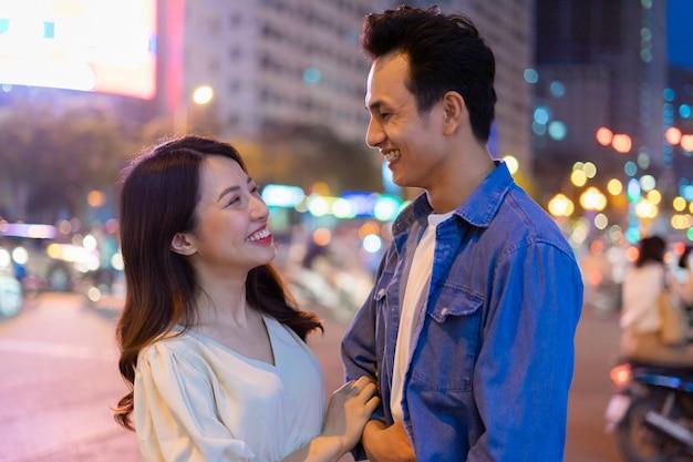 Jeune couple asiatique marchant dans la rue pendant la nuit