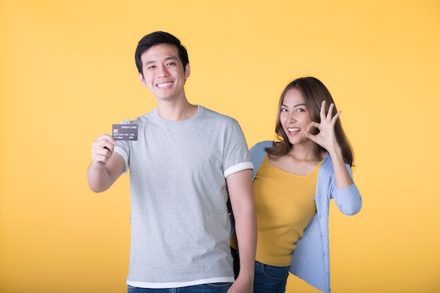 Jeune couple asiatique montrant une carte de crédit isolée sur un mur jaune