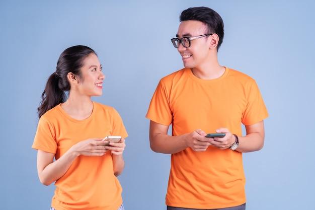 Jeune couple asiatique portant un t-shirt orange sur fond bleu