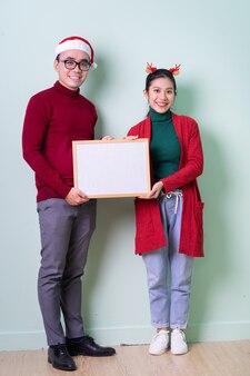 Jeune couple asiatique posant sur fond vert avec concept de noël