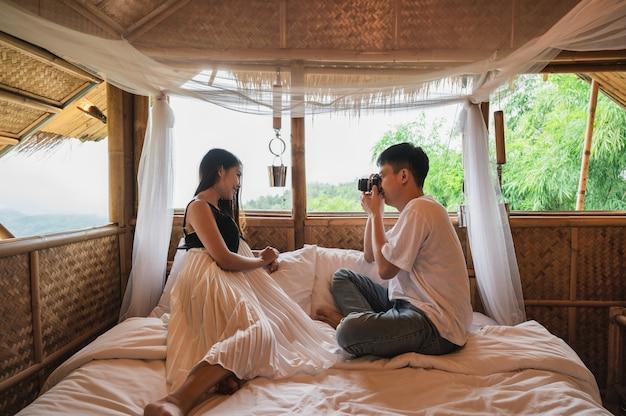 Un jeune couple asiatique prend une photo avec un appareil photo rétro sur le lit dans une cabane en bois au milieu de la nature en vacances