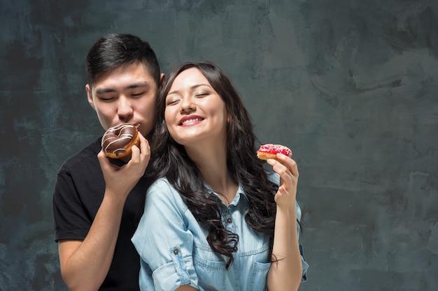 Jeune couple asiatique profiter de manger du beignet coloré sucré