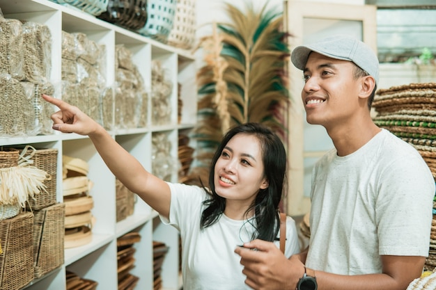 Un jeune couple asiatique recherche et sélectionne les produits artisanaux qu'ils souhaitent acheter dans une boutique d'artisanat
