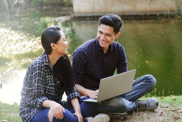 Jeune couple asiatique s'amuser avec un ordinateur portable