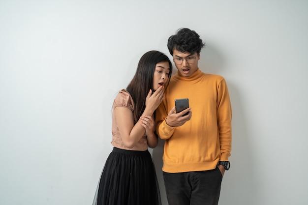 Jeune couple asiatique se tenait en regardant l'écran d'un téléphone intelligent avec une expression étonnée
