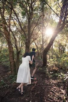 Jeune couple asiatique se tenant la main en randonnée dans la forêt avec la lumière du soleil au parc national