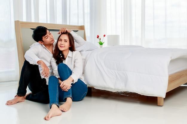 Jeune couple asiatique séduisant et heureux portant une chemise blanche propre, assis ensemble sur le sol dans la chambre avec fond de rideau blanc. concept d'amour et de relation heureuse.