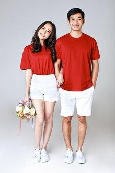 Jeune couple asiatique séduisant portant un t-shirt rouge et un short blanc, debout ensemble, femme tenant un bouquet de fleurs sur fond blanc. concept pour la photographie avant le mariage. isolé.