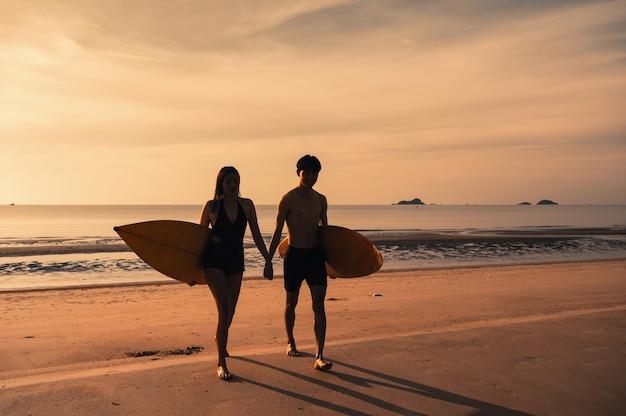 Jeune couple asiatique tenant une planche de surf sur la plage au matin