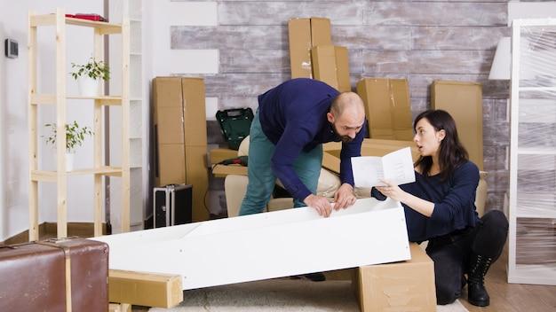 Jeune couple assemblant des meubles en équipe dans un nouvel appartement. fille lisant les instructions de montage.