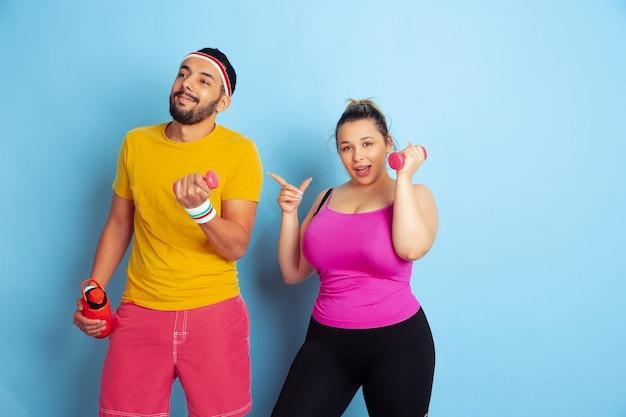 Jeune couple assez caucasien en formation de vêtements lumineux sur fond bleu concept de sport, émotions humaines, expression, mode de vie sain, relation, famille. entraînement avec des poids, amusez-vous.