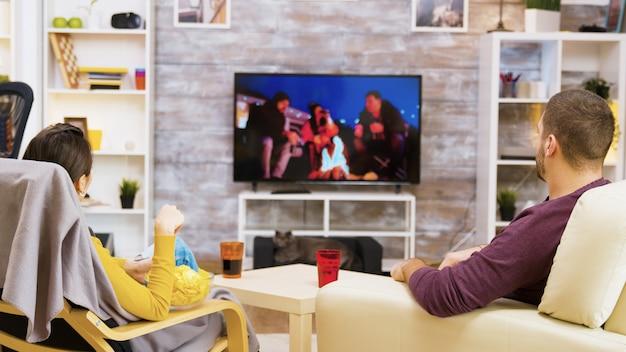 Jeune couple assis à l'aise devant la télévision en train de manger des chips et du pop-corn en regardant leur chat.