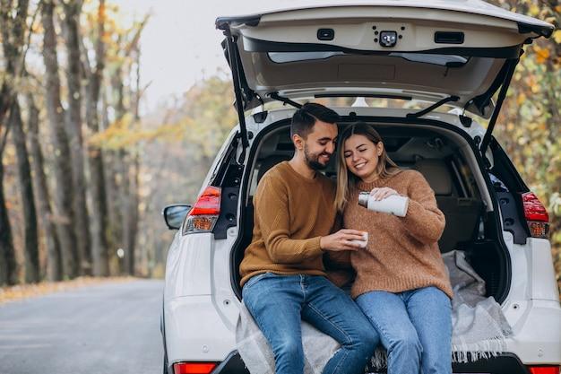 Jeune couple assis à l'arrière d'une voiture, buvant du thé en forêt