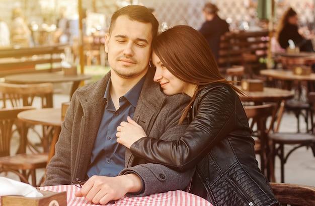 Jeune couple assis au café de rue dans la lumière du soleil.