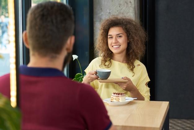 Jeune couple assis au restaurant, boire du café, souriant, parler.
