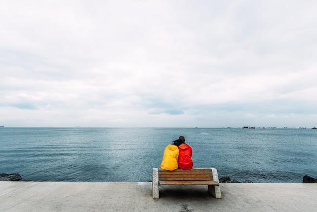 Jeune couple assis sur un banc au bord de la mer. homme et femme voyageant. les gens s'assoient sur un banc et regardent la mer. touristes à la mer. amis sur le banc. un couple solitaire. marcher le long de la promenade