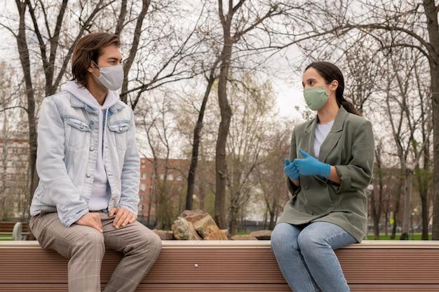Jeune couple assis sur un banc dans le parc et gardant la distance tout en se parlant pendant la période du coronavirus
