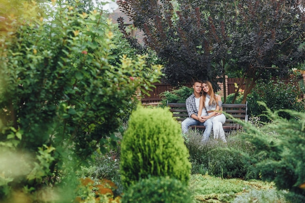 Jeune couple assis sur un banc dans le parc et regardant à l'avant