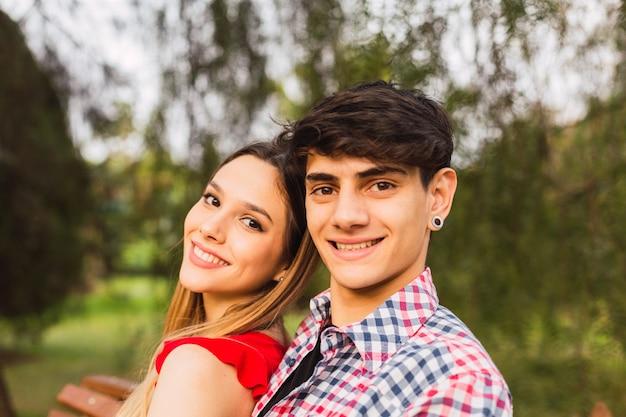 Jeune couple assis sur un banc et souriant à la caméra.