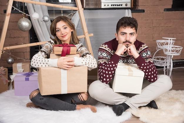 Jeune couple assis avec des cadeaux de noël près des boules d'argent festives.
