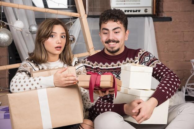 Jeune Couple Assis Avec Des Cadeaux De Noël Près Des Boules D'argent Festives. Photo gratuit