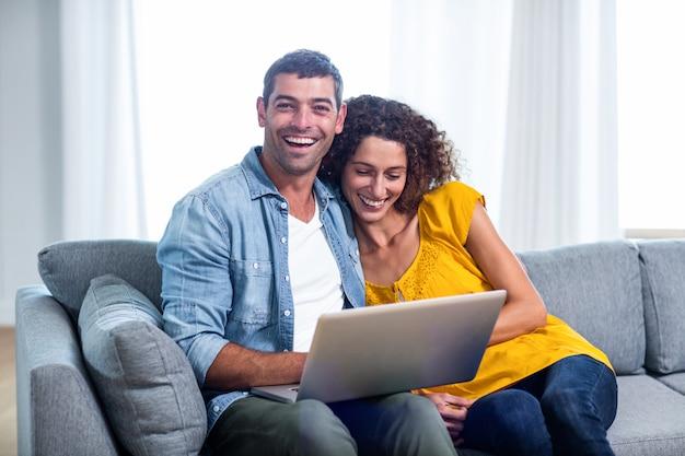 Jeune couple assis sur un canapé et à l'aide d'un ordinateur portable
