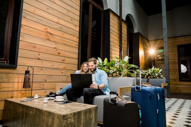 Jeune couple assis sur un canapé dans le hall de l'hôtel à l'arrivée, à l'aide d'un ordinateur portable, souriant heureux.