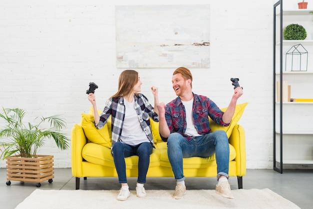 Jeune couple assis sur un canapé jaune dans le salon, acclamations après avoir joué au jeu vidéo