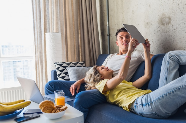 Jeune couple assis sur un canapé à la maison à la recherche de tablette, regarder en ligne