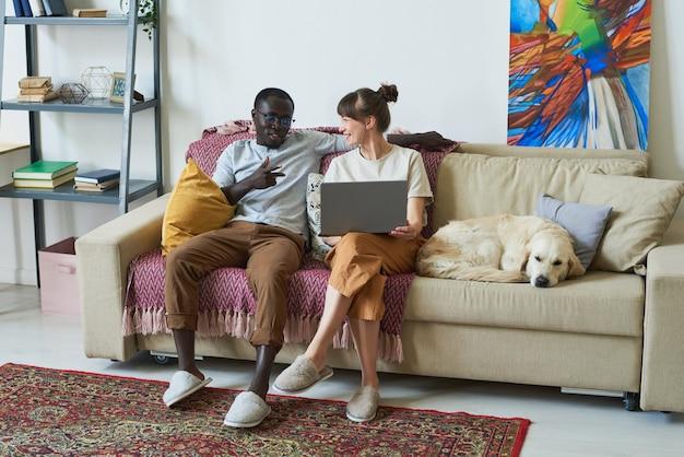 Jeune couple assis sur un canapé avec un ordinateur portable et se parlant dans la chambre à la maison