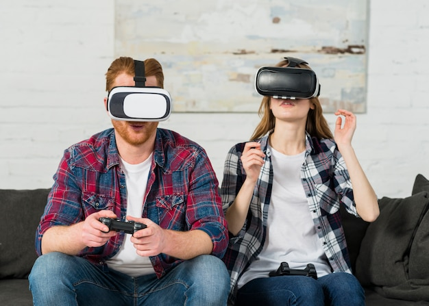 Jeune couple assis sur le canapé pendant l'expérience vr jouant le joystick