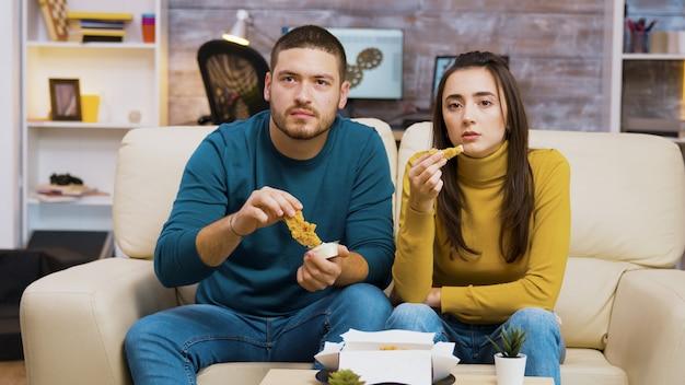 Jeune couple assis sur un canapé en train de manger du poulet frit en regardant la télévision.