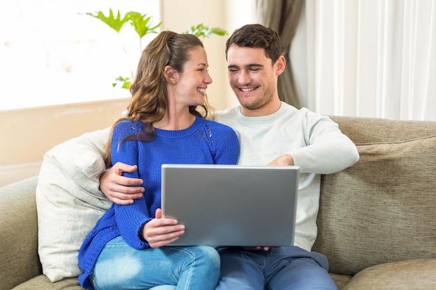 Jeune couple assis sur un canapé et utilisant un ordinateur portable dans le salon