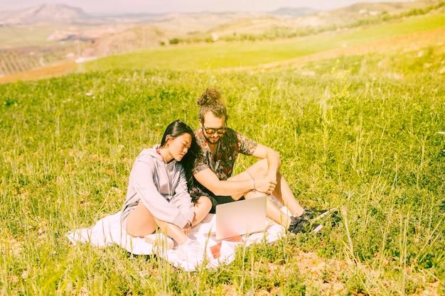 Jeune couple assis dans le champ avec un ordinateur portable
