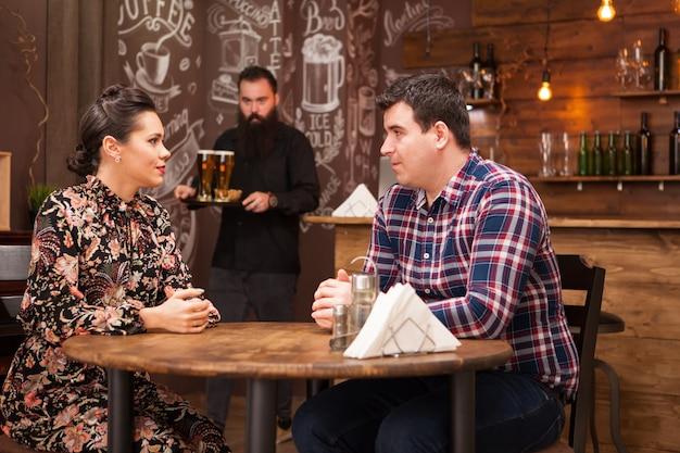 Jeune couple assis dans un restaurant parlant et s'amusant.
