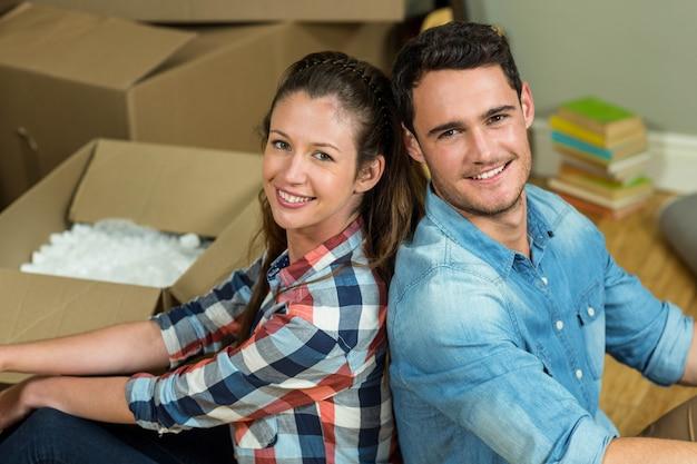 Jeune couple assis dos à dos et se regardant dans leur nouvelle maison