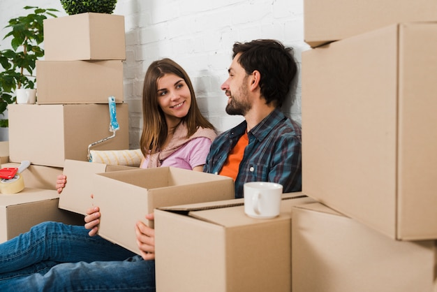 Jeune couple assis entre les cartons se regardant
