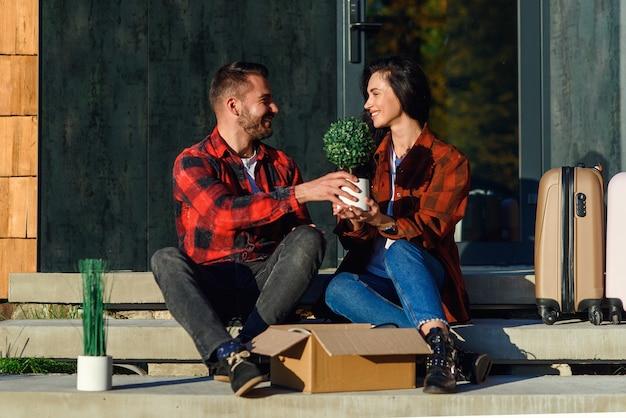 Jeune couple assis sur les escaliers s'amusant à déballer les boîtes après avoir déménagé dans une nouvelle maison.