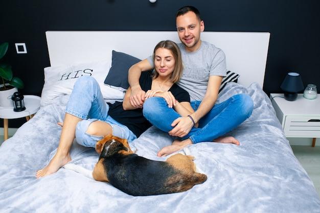 Jeune couple assis sur un lit dans la chambre, étreignant. près d'eux est leur chien