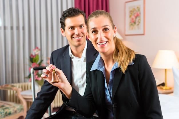 Jeune couple assis sur un lit dans une chambre d'hôtel