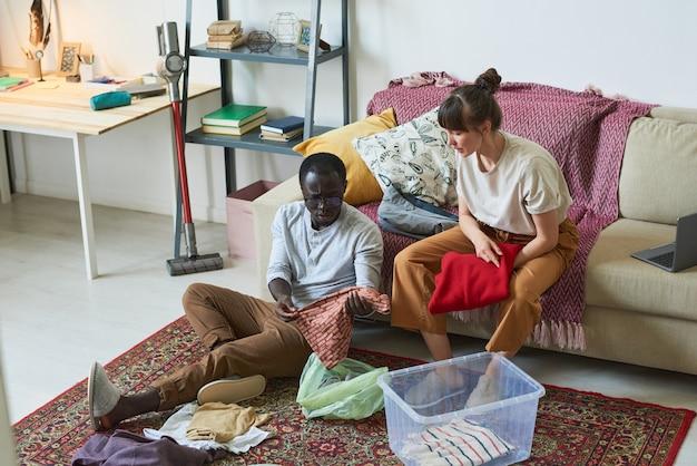 Jeune couple assis par terre dans la chambre et ranger ses vêtements