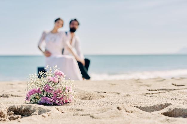 Jeune couple assis sur la plage habillé en mariés avec un bouquet de fleurs sur le sable
