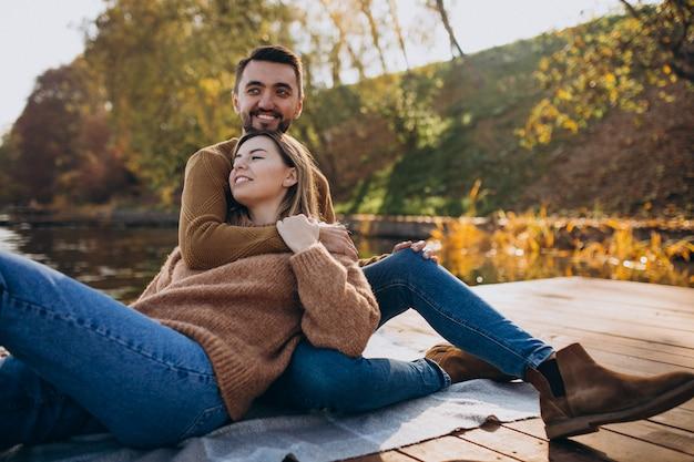 Jeune couple assis sur le pont en bord de rivière