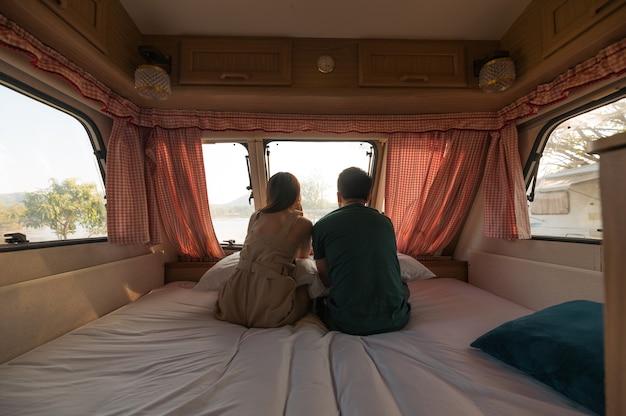 Jeune couple assis et prenant une vue sur le matelas à l'intérieur du camping-car