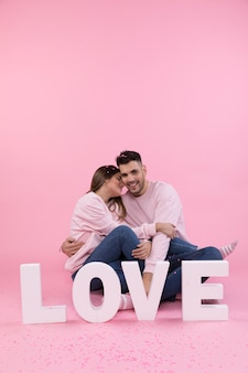 Jeune couple assis près de gros signe d'amour et confettis