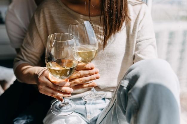 Jeune couple assis sur le rebord de la fenêtre, étreindre et boire du vin